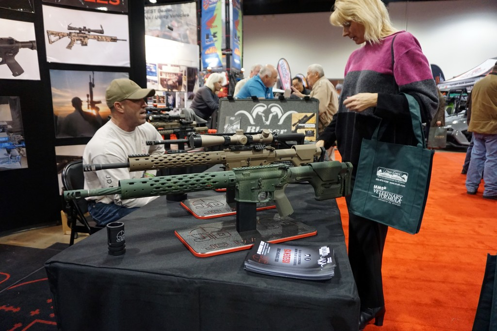 A woman looks at guns built by JD Machinetech at the expo. Photos by George Demopoulos.