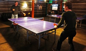 Punch Bowl customers play ping-pong.