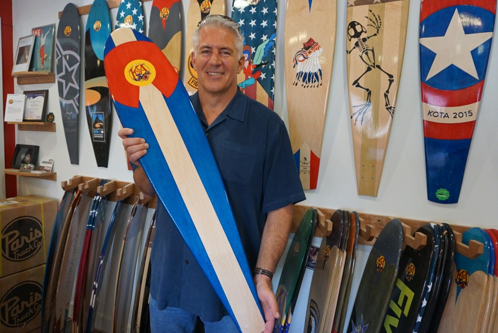 Mike Maloney shows off one of his company's longboards. Photos by George Demopoulos.