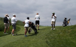 Caddies haul bags up a hill at CommonGround.