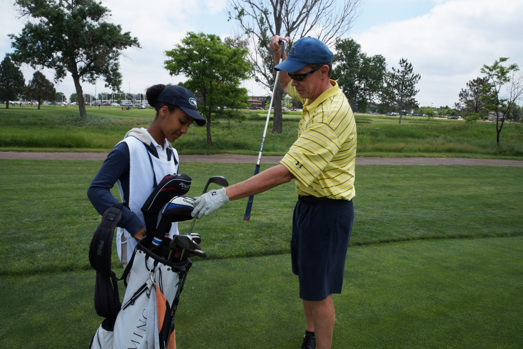 Helena Seyoum hands off a new club to golfer Mark Brorby. Photos by Katherine Blunt.