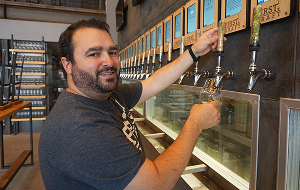 Mark Slattery pours a beer from one of his 40 self-serve taps. Photos by George Demopoulos.